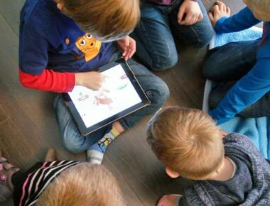Kinder spielen am Tablet.