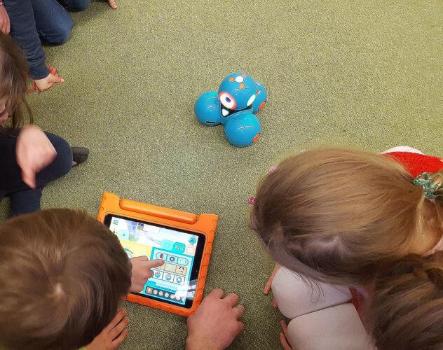 Kinder spielen mit Roboter.