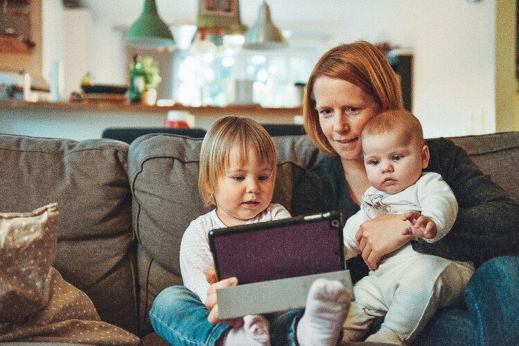Mutter sitzt mit Kindern auf der Couch und schaut auf das Tablet.