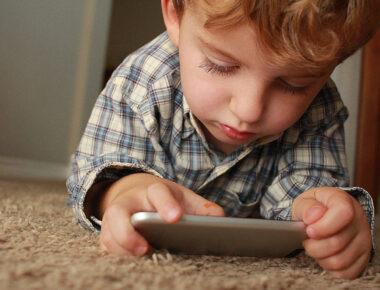 Kind liegt auf dem Boden und schaut auf ein Smartphone.