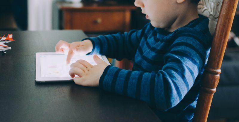 Kind sitzt am Tisch und schaut aufs Tablet.