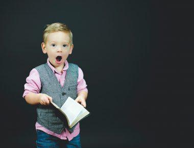 Kind mit Buch in der Hand reißt überrascht den Mund auf